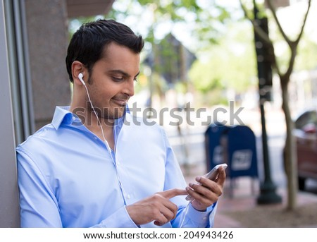 Closeup portrait, young happy business man standing, checking his cellphone, listening to music, isolated on background of a city road with trees on a sunny autumn day. Corporate life success. - stock photo