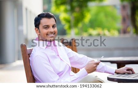 Closeup portrait, young happy businessman sitting, checking his cellphone, isolated on background of a city building, trees, on a sunny autumn day. Corporate life success. Business communication - stock photo