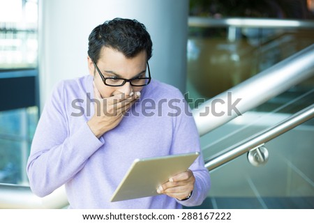 Closeup portrait, young happy man in black eyeglasses and purple sweater, astonished, hand on mouth concealed laugh, by what he sees on tablet, isolated indoors office background - stock photo