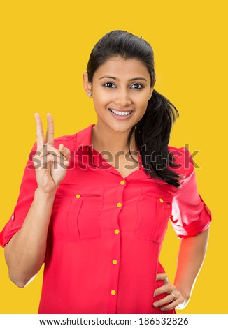Closeup portrait, young, happy, smiling, confident, excited woman giving peace victory or two sign gesture, isolated yellow background. Positive emotion facial expression feelings symbols, attitude - stock photo