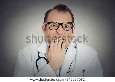 Closeup portrait young insecure, crazy male doctor uncertain psychiatrist with glasses looking funny, scared, craving anxious isolated grey background. Human face expression emotion feeling perception - stock photo