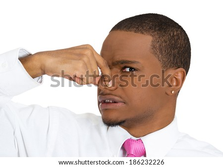 Closeup portrait, young man, disgust on his face, pinches his nose looks at you, something stinks, very bad smell, situation, isolated white background. Negative emotion facial expression feeling