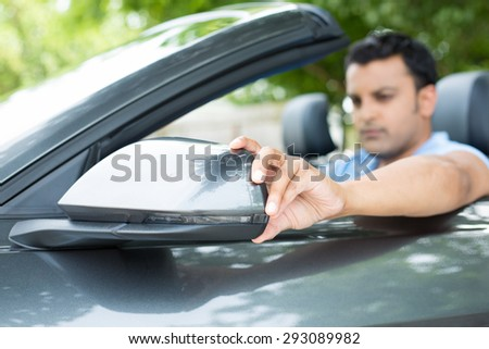 Closeup portrait, young man driver looking adjusting side view car mirror, making sure he can see traffic OK around him, isolated outdoors background - stock photo