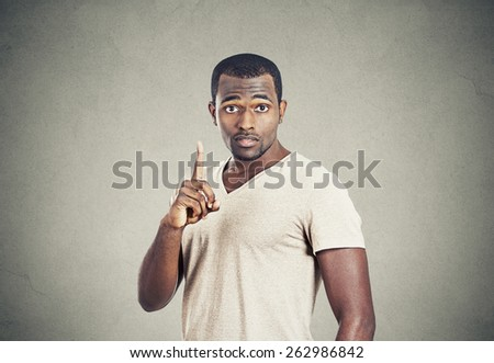 Closeup portrait young man pointing up having idea, solution, showing with index finger number one isolated grey wall background. - stock photo