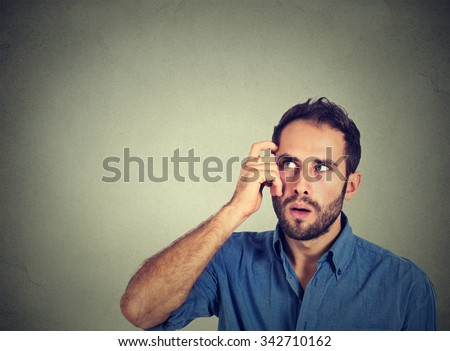 Closeup portrait young man scratching head, thinking deeply about something, looking up, isolated on grey wall background. Human facial expression, emotion, feeling, sign body language - stock photo