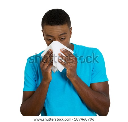 Closeup portrait, young man, sick guy, student, worker patient with allergy, cold blowing his nose, kleenex, looking miserable unwell, isolated white background. Flu season, vaccination - stock photo