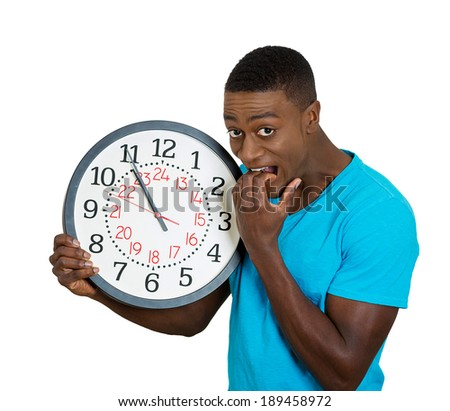 Closeup portrait, young man, student, leader holding a clock very stressed, pressured by lack of time running out, late for the meeting, isolated on white background. Negative facial expression - stock photo