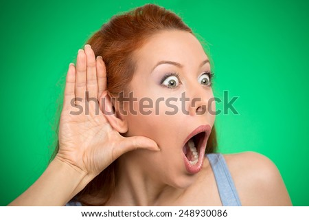 Closeup portrait young nosy woman hand to ear gesture shocked carefully intently secretly listening on juicy gossip conversation news privacy violation isolated green background. Human face expression - stock photo