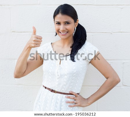 Closeup portrait, young pretty smiling woman, student,customer giving thumbs up sign, isolated white brick background. Positive human emotion, facial expression feelings, signs, symbols, body language - stock photo