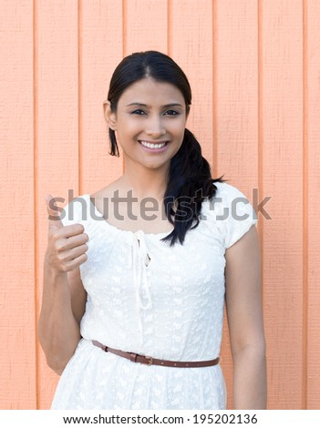 Closeup portrait, young pretty smiling woman, student,customer giving thumbs up sign, isolated orange wood background.  - stock photo