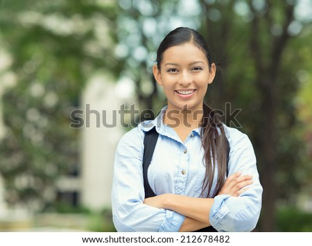 Closeup portrait, young professional, beautiful confident businesswoman in blue shirt smiling isolated outdoor trees background. Positive human emotions, facial expressions, attitude, life perception - stock photo