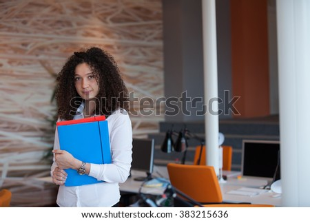 Closeup portrait, young professional, beautiful confident woman in blue shirt, arms crossed folded, smiling isolated indoors office background - stock photo