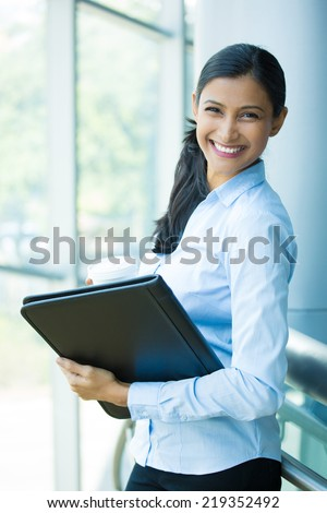 Closeup portrait, young professional, beautiful confident woman in blue shirt, holding coffee and black notebook, smiling isolated indoors office background. Positive human emotions - stock photo