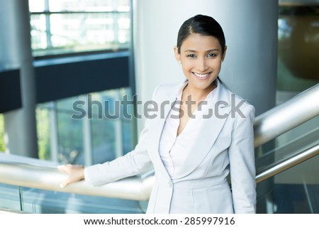 Closeup portrait, young professional, beautiful confident woman in gray white suit, friendly personality, holding rail, smiling isolated indoors office background. Positive human emotions - stock photo