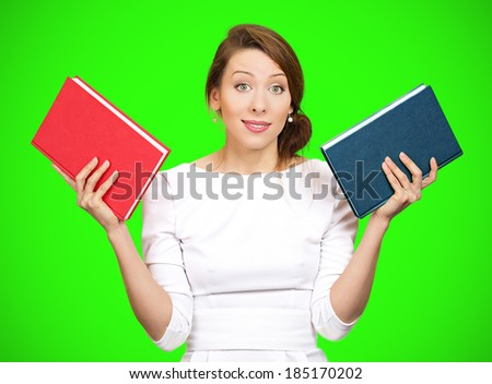 Closeup portrait young serious business woman, confused student holding red, blue book in hands, thinking, deciding which one to choose, way to go, isolated green background. Emotions, expressions