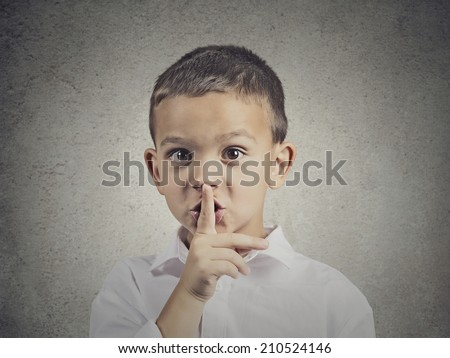 Closeup portrait young serious child, boy placing finger on lips as if to say, shhh, be quiet, silence, isolated grey wall background. Facial expression, human emotions, signs, symbols, body language - stock photo