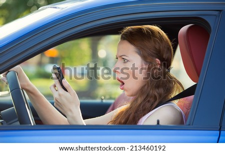 Closeup portrait, young shocked, stressed woman driver, driving in car checking smart phone annoyed by bad text message email isolated outside street background. Negative human emotion face expression - stock photo