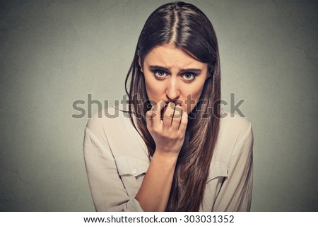 Closeup portrait young unsure hesitant nervous woman biting her fingernails craving for something or anxious, isolated on gray wall background. Negative human emotions facial expression feeling - stock photo