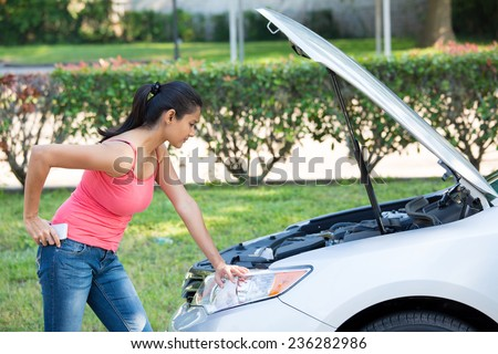 Closeup portrait, young woman in pink tanktop having trouble with her broken car, opening hood and looking at engine to see whats wrong, isolated green trees and shrubs outside background - stock photo