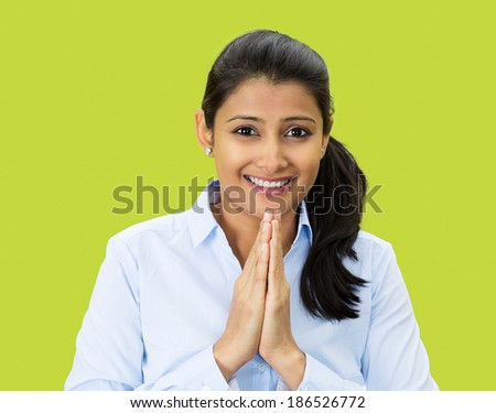 Closeup portrait, young woman praying looking at you, in gratitude, thankfulness and hope, isolated green background. Positive human emotions, facial expression feelings, reaction - stock photo