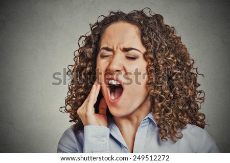 Closeup portrait young woman with sensitive tooth ache crown problem about to cry from pain touching outside mouth with hand isolated grey wall background. Negative emotion facial expression feeling - stock photo