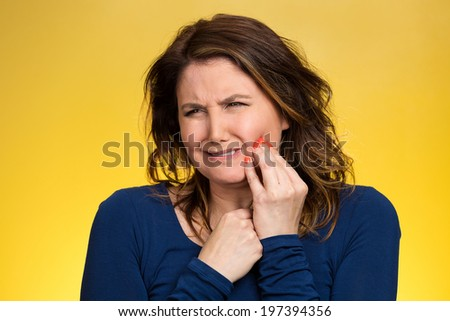 Closeup portrait young woman with sensitive tooth ache, crown problem crying from pain, touching outside mouth with hand isolated yellow background. Negative emotion, facial expression feeling, health - stock photo