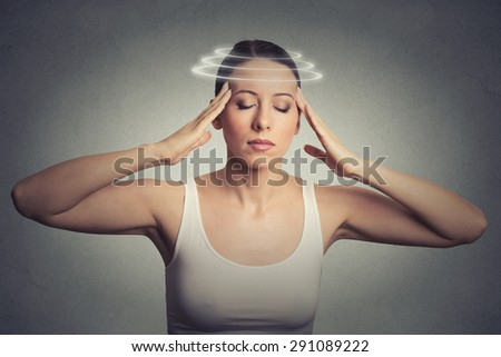 Closeup portrait young woman with vertigo. Young female patient suffering from dizziness isolated on gray wall background  - stock photo