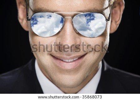 Closeup portret of handsome pilot in glasses. Sky reflected in glasses. - stock photo