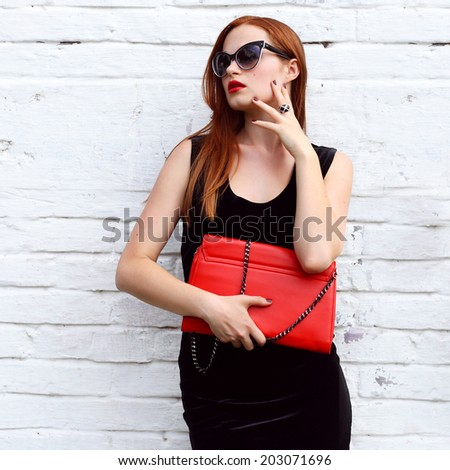 closeup potrait gorgeous fashion young woman looking away and posing in black fashionable dress , sunglasses, red handbag near street white wall - stock photo