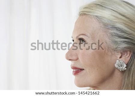 Closeup profile of a beautiful senior woman against white background - stock photo