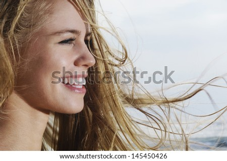 Closeup profile of a smiling young woman looking away with blond hair blowing in wind - stock photo