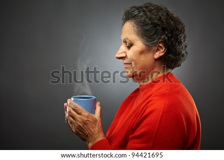 Closeup profile of an elderly senior woman with hot coffee or tea in a cup, on gray background