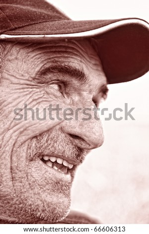 Closeup Profile on a Smiling Old Man With a Cap on Head - stock photo
