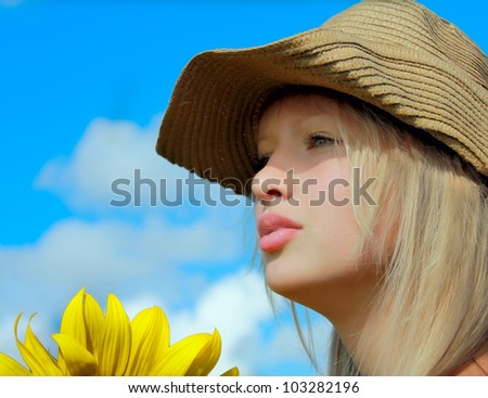 Closeup profile portrait of young girl in a hat with sunflower - stock photo