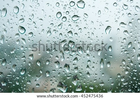 Closeup Rain drops on window glass against blurred city background. Viewpoint from inside a building. Summer rainy day. Detail natural of rain drops or abstract background. - stock photo