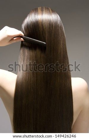 Closeup rear view of a woman combing her long brown hair against gray background - stock photo