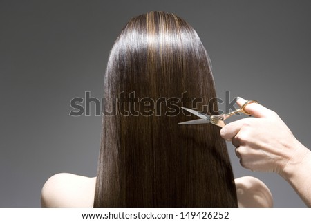 Closeup rear view of a woman having a haircut against gray background