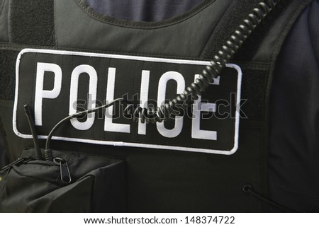Closeup rear view of policeman's sign and cord on protective jacket - stock photo