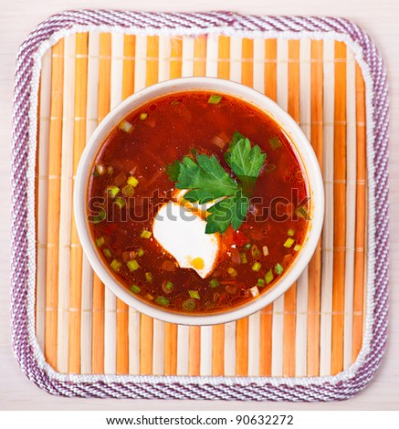 closeup red borscht (soup) in deep bowl is decorated with cream and parsley on the background of napkin - stock photo