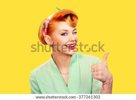 Closeup red head young woman pretty pinup girl green button shirt giving thumbs up sign gesture looking at you camera isolated yellow background retro vintage 50's style. Human emotions body language - stock photo