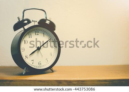 Closeup retro alarm clock on table with blurred white brick background. Selective focus, Vintage filter - stock photo