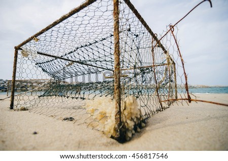closeup rusty crab pots on the sandy beach over blurred water break background.focus in the middle.shallow depth of field.color toning effect - stock photo