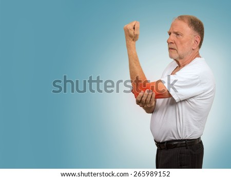 Closeup senior man with elbow inflammation colored in red suffering from pain and rheumatism isolated on light blue background with copy space  - stock photo