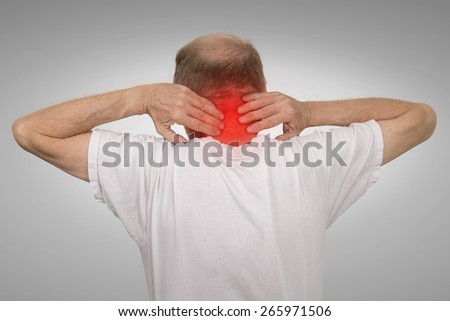 Closeup senior mature man with bad neck spasm pain touching colored in red inflamed area suffering from arthritis isolated on gray wall background. Human health problems, geriatrics medicine concept  - stock photo