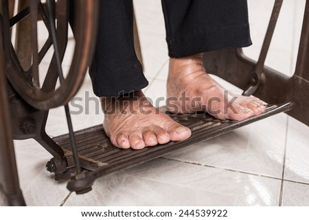 closeup senior tailor's feet working on vintage sewing machine - stock photo