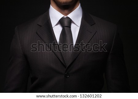closeup shoot of businessman on dark background - stock photo