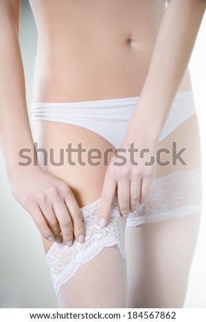 Closeup shoot of female hands adjusting the white stockings