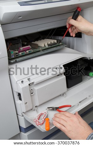 closeup shot hands of technician fixing a broken photocopier machine