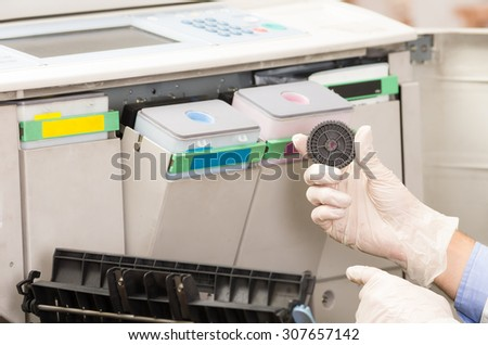 closeup shot hands of technician fixing broken photocopier machine