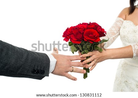 Closeup shot of a bride presenting a rose bouquet to the groom.
